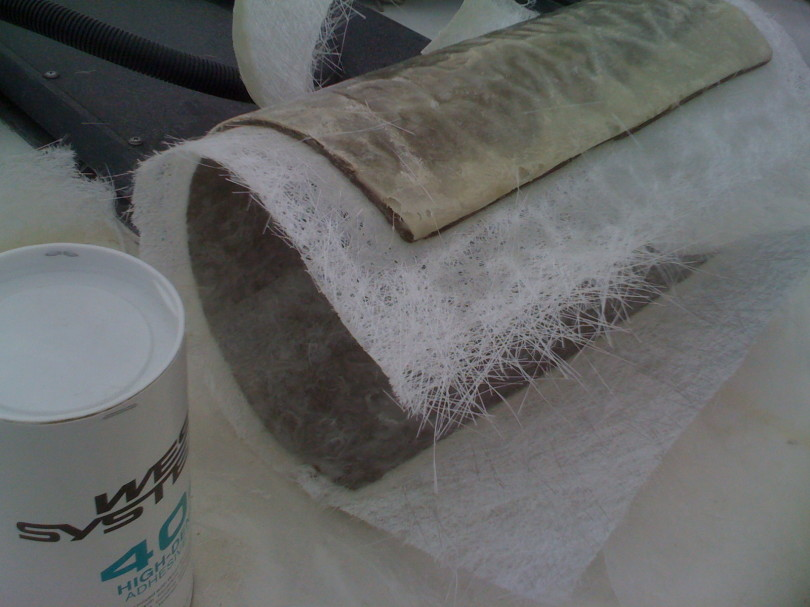 Cardboard tube wet out with epoxy resin and layers of fiberglass layed on.